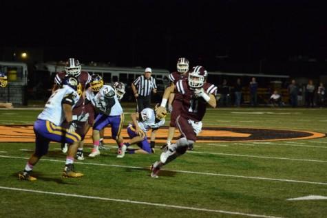 Ada quarterback, Gabe Simons (11), runs the ball, dodging the Bristow defense.
