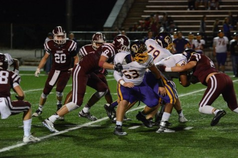 Vaughn Appleman (8) drags down a Bristow player while Christian Maloy (2) makes the tackle.