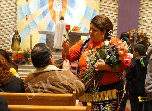 Gaby Valles handing out roses to the people to place to Virgin De Guadalupe