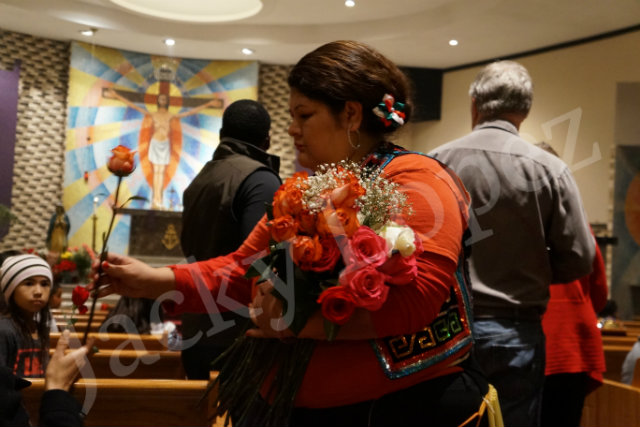 Dancers handing out roses to the people to place to Virgin De Guadalupe