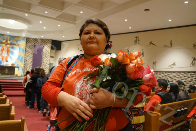 Gaby Valles poses while out roses to people