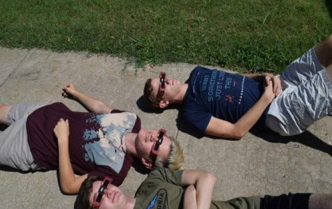 William Pottebaum, Bryan Moses, and Westin Williams watch the eclipse. They relaxed on the sidewalk and enjoyed their front row seats.