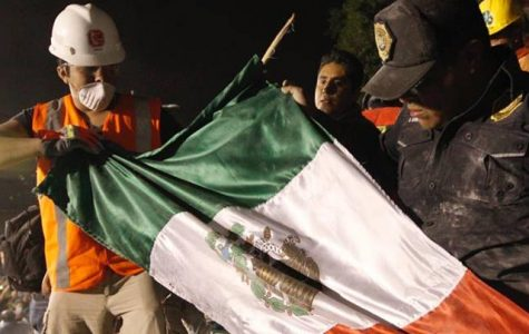 Mexican Authorities and rescuers pull the Mexican flag out of the rubble
