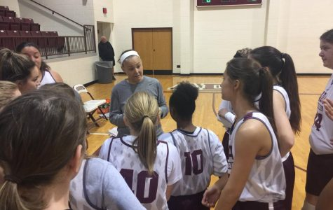 Head coach Christie Jennings huddles with her team during a pre-season scrimmage.