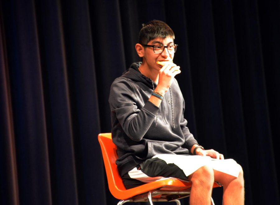 Carlos Lerma displays his talent for Rush Week by eating a Bean Burrito as to draw laughter from audience.