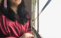 Using a timer, senior Karla Charqueno captures a photo of herself in her cap and gown. Charqueno imagined a very different end to her senior year than spending it in quarantine.