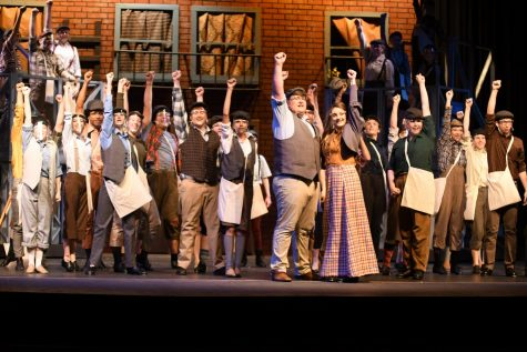 The cast of Newsies performs the finale of the show during the Newsies Square scene.